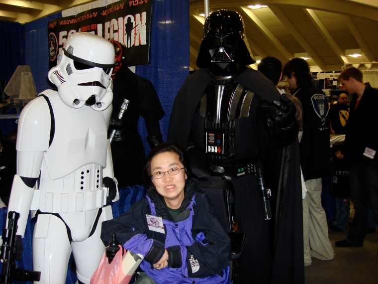 Photo of an Asian-American wheelchair user next to an Imperial Stormtrooper and Darth Vader