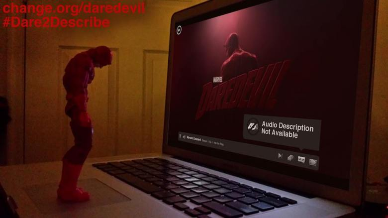 "A Daredevil action figure stands on a laptop keyboard, his head and shoulders slumped down dejectedly. On the screen is the opening sequence from the Netflix series Marvel's Daredevil with an alert window that reads: ""Audio Description Not Available."""